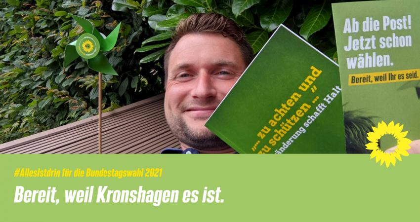 Auf dem Bild sieht man Vorstandsmitglied Christian Schall, wie er einige Materialien und Giveaways zur Bundestagswahl hochhält.